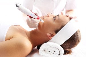 Beautician performs a needle mesotherapy treatment on a woman's face
